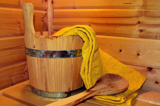 the benefits of a sauna and cold plunge - wooden tub, towel and paddle