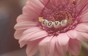 The Origins of Mothering Sunday - pink flower with love bracelet on it