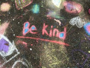 The words Be Kind chalked on a pavement. - Ways in which to be kind